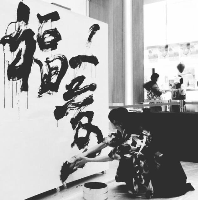 giapponese mentre si esprime attraverso l'arte calligrafica